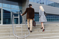 Businessman and businesswoman, walking up steps together, rear view