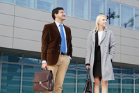 Businessman and businesswoman, standing together, outdoors