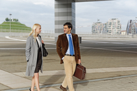 Businessman and businesswoman, walking together, outdoors
