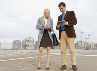 Businessman and businesswoman outdoors, holding digital tablets, sharing information