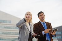 Businessman and businesswoman outdoors, holding digital tablets, looking lost
