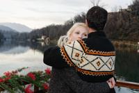 Heterosexual couple embracing beside lake, Lombardy, Italy