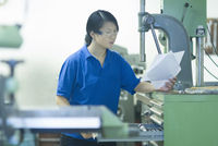Young woman holding papers in industrial workshop