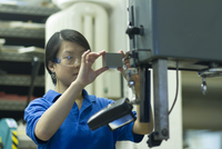 Young woman holding component in industrial workshop