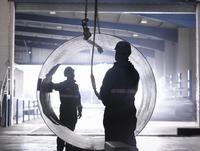 Engineers using crane to lift large steel tube in engineering factory