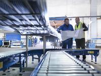 Engineers inspecting new conveyor in engineering factory