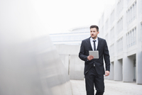 Suited young businessman walking with digital tablet outside office