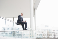 Suited young businessman sitting on office railings using digital tablet