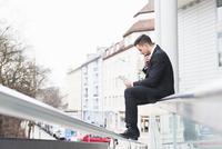 Suited businessman sitting on office railings using digital tablet