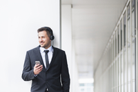 Young businessman outside office listening to smartphone music on headphones