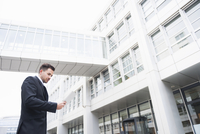 Young businessman reading digital tablet whilst walking outside office