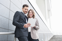 Young businessman and woman using digital tablet on stairway outside office