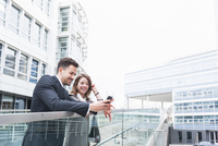 Young businessman and woman reading smartphone texts on footbridge outside office