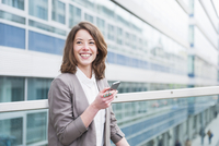 Confident young businesswoman using smartphone on footbridge outside office
