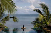 Rear view of mid adult woman relaxing in infinity pool, Koh Samui, Thailand
