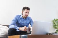 Young man sitting on sofa looking at laptop 11015249815  写真素材・ストックフォト・画像・イラスト素材 アマナイメージズ