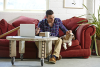 Mid adult man writing address on parcels whilst petting dog in picture framers