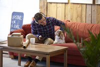 Mid adult man petting dog in picture framers showroom