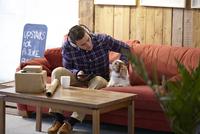 Mid adult man petting dog in picture framers showroom 11015249861  写真素材・ストックフォト・画像・イラスト素材 アマナイメージズ