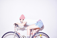 Studio shot of young woman leaning forward on bicycle