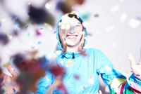 Studio shot of young woman scattering confetti