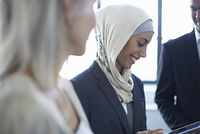 Over shoulder view of businesswomen and man chatting in office 11015250076| 写真素材・ストックフォト・画像・イラスト素材|アマナイメージズ