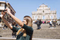 Young female tourist taking smartphone selfie in front of St Pauls Cathedral ruins, Macau, Hong Kong, China
