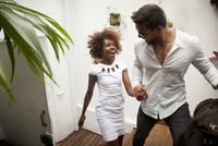 Couple arriving into apartment, holding hands 11015250327| 写真素材・ストックフォト・画像・イラスト素材|アマナイメージズ