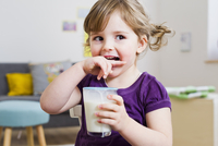 Girl holding glass of milk at home