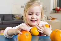 Girl taking oranges from table