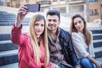 Young woman taking smartphone selfie with friends on stairway, Cagliari, Sardinia, Italy