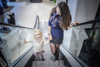 Mother and young daughter moving up escalator in shopping mall