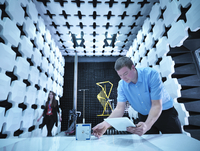 Engineers checking equipment under test (EUT), a continuous noise source in fully anechoic chamber with energy absorbers and bil