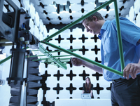 Engineers checking a bilog antenna for electromagnetic compatibility (EMC) radiated immunity testing in a semi anechoic chamber