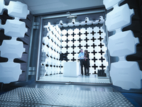 Engineers reviewing test results in laboratory in an anechoic chamber used for electromagnetic compatibility testing of electric