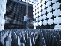 Engineer in anechoic chamber with horn antenna set up for Electromagnetic compatibility (EMC) radiated emission testing