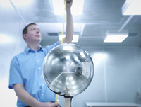 Engineer checking height of equipment under test (EUT) with Van Der Hoofden Head used during electromagnetic field (EMF) safety