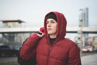 Young man wearing red hooded anorak on city street 11015251370| 写真素材・ストックフォト・画像・イラスト素材|アマナイメージズ