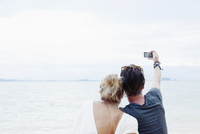 Rear view of young couple taking smartphone selfie on beach, Kradan, Thailand