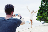 Young man photographing girlfriend jumping on beach, Kradan, Thailand