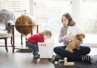 Boy playing at home with mother and baby sister