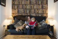 Mother reading book to son on sofa