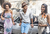 Three friends standing together, leaning against car