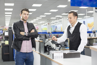 Unsure shopper paying with credit card in electronics store