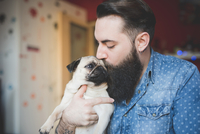 Young bearded man kissing dog in arms