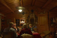 Three generation family sitting talking at Christmas table in log cabin at night