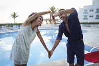 Stylish couple making heart shape with arms at poolside, Rio De Janeiro, Brazil