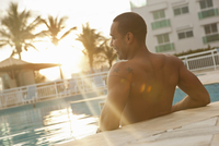 Rear view of mid adult man standing in sunlit hotel swimming pool, Rio De Janeiro, Brazil