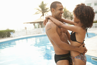 Smiling couple hugging at hotel poolside, Rio De Janeiro, Brazil