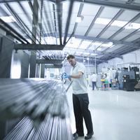 Engineer inspecting steel rods in factory